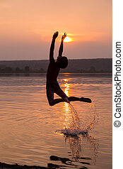 Boy jumping into water on sunset