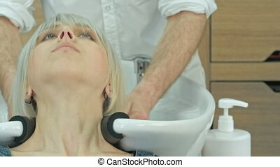 Happy young woman with hairdresser washing head at hair...