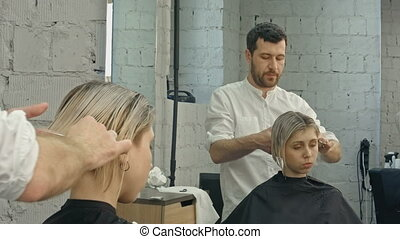 Professional hairdresser with short hair model. Professional...