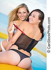 Two joyful women in lingerie posing on the yellow pool
