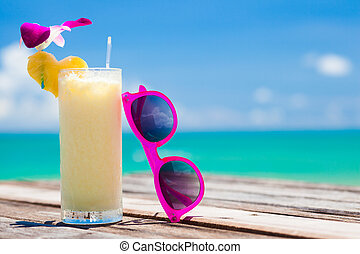 fresh exotic banana and pineapple cocktail and sunglassses on a wooden table by the beach