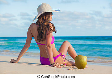 young long haired woman in straw hat with coconut on the beach