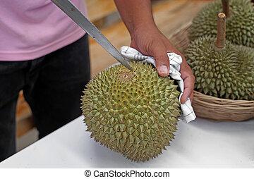 vendor peeling durian for customer in fruit market