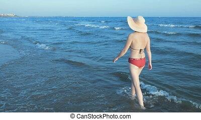Woman in bikini with straw sun hat walking beach - Woman in...