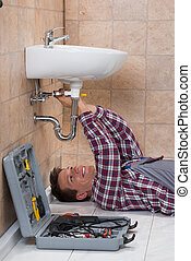 Plumber Lying On Floor Fixing Sink - Happy Young Male...