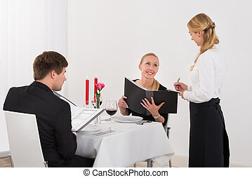 Waitress Taking An Order From A Happy Couple