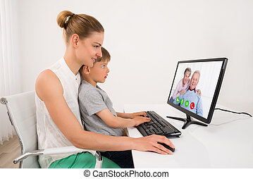 Mother And Son Videoconferencing On Computer At Home