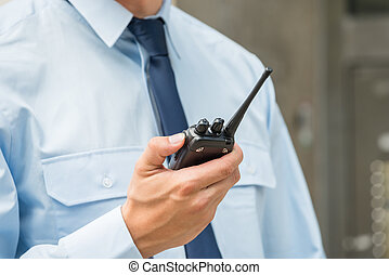 Security Guard Holding Walkie-talkie - Close-up Photo Of...