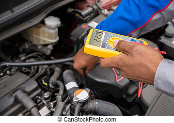 Mechanic Checking Battery With Multimeter - Close-up Of...