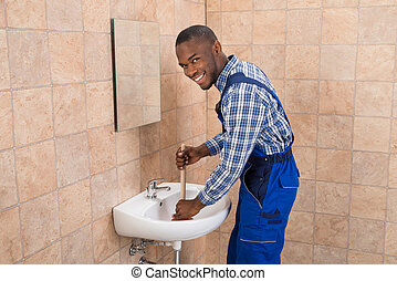 Plumber Using Plunger In Bathroom Sink - Happy Young African...