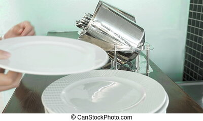 Taking white plate and putting on fork and knife - Person's...