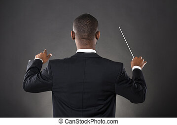 Conductor Directing With His Baton - Young African Conductor...