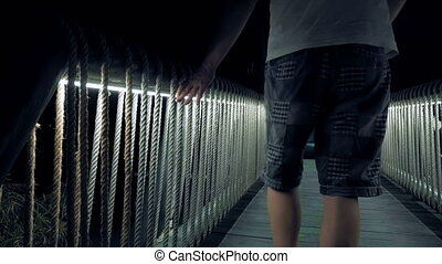 Men walking over the lighted wooden bridge - Men walking...