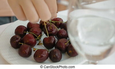 Sweet cherry with glass of water in foreground - Persons...