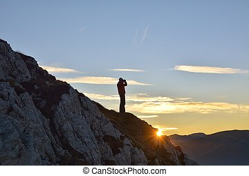Man stands on the peak of sandstone rock in national park...