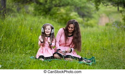 daughter and mother headphones - Mom with her daughter and...