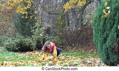 Happy gardener woman throwing colorful autumn leaves in park. 4K