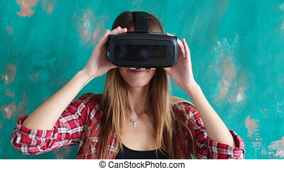 Young woman playing video game with cardboard virtual...