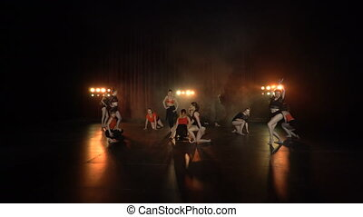 Dance performance of female group on a stage with lights and...