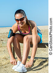 Female runner tying shoe lace outdoors - Close up portrait...