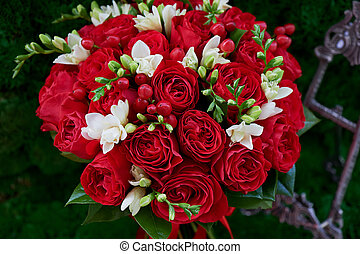 dense red bouquet of roses, with berries and decor. Close -...