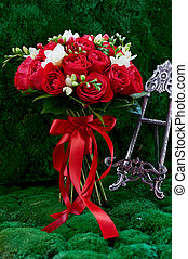 dense red bouquet of roses, tied with a ribbon. Close -...