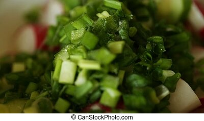 Stirring salad vegetables: radishes, cucumber, green onion,...