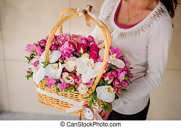 girl holding beautiful pink bouquet of mixed flowers in...