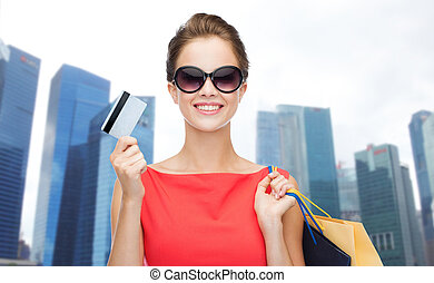 woman with shopping bags and credit card over city - people,...