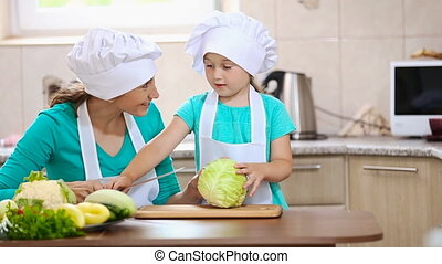 mother with her daughter cut cabbage - mother with her...