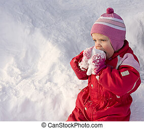 Cute little toddler (2 years old) eating snow.