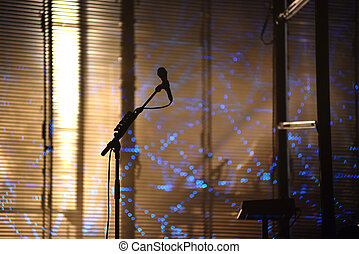 Microphone on stage with stage-lights in the background
