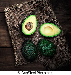Halved and whole avocado on a dark wood background. Rustic...