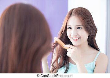 young woman is combing hair