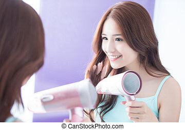 young woman is blowing hair