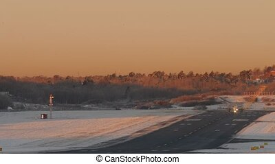 Airplane takes off from snowy airport in Sweden. Beautiful early moning light