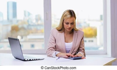 businesswoman with laptop, calculator and papers - business,...