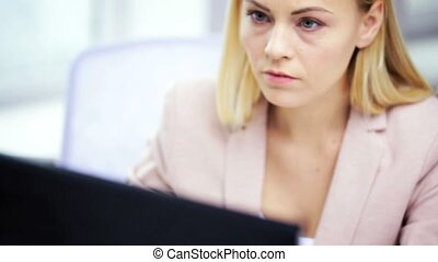 stressed businesswoman with computer at office - business,...