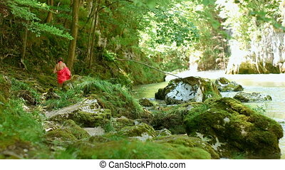 Young Adult Walking Towards the River - Female in the red...