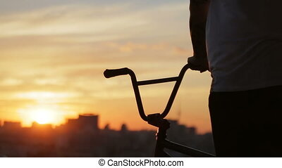 Boy preparing for the ride with his bmx looking at sunset.
