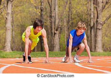Two teenage boys ready to start running on a track