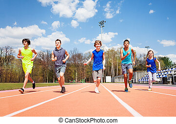 Five teenage sprinters running together on a track