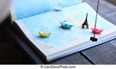 Travel to World idea or Tourism. Paper boats on the map and the Eiffel Tower.