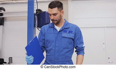 mechanic man with clipboard at car workshop 18 - car...