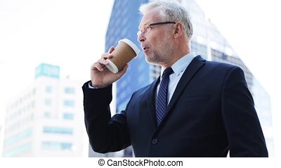 senior businessman drinking coffee on city street -...