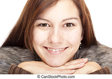 young Woman with chin on hands smiling happy into camera