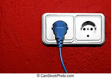 plugging - blue cord plugged on a white outlet on a red wall