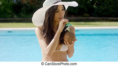 Beautiful woman sipping a coconut cocktail
