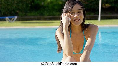 Exotic brunette smiles as she talks on cell phone