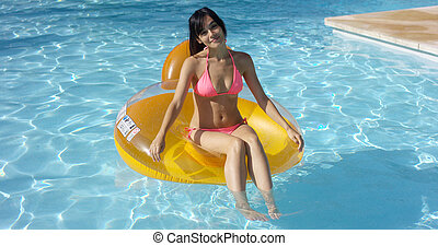 Lovely young woman floating in a swimming pool